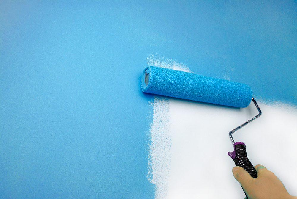תהליך שיפוצים יד של אדם צובעת קיר, בררו על מחיר צביעה לדירה 4 חדרים